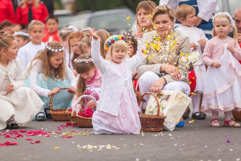 Dzieci uczestniczące w procesji sypią kwiaty w miejscach gdzie nie ma kwietnego chodnika