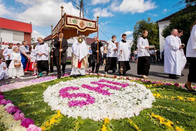 Kapłan niosący Przenajświętszy Sakrament ulicami wsi