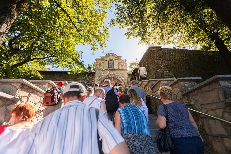 Pielgrzymi witani oraz kropieni wodą święconą przez franciszkanina